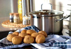 Topf auf dem Herd mit Kartofffeln in der Küche