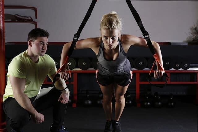 Frau trainiert im Fitnessstudio mit einem Fitnesstrainer